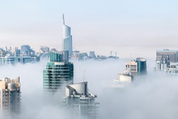 Morning fog hovering skyscrapers at sunrise. Aerial view of building rooftops over the clouds in Dubai Marina