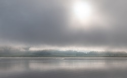 Morning fog over a lake surrounded by hills. The calm expanse of water under thick clouds. Gorny Altai (Mountain Altay), South Siberia, Russia