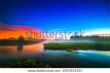 Morning fog over a rural river. Early morning river fog. Fog on the river at dawn. Early morning foggy river at dawn