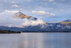 morning fog rising over calm Lake Dillon in Colorado Rocky Mountains