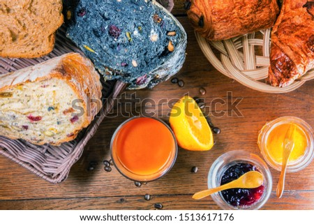 Morning good mood with a good varied breakfast 3 varieties of breads with dried fruits and cereals and bran and charcoal, croissant and chocolate bread fresh orange juice honey and strawberry jam
