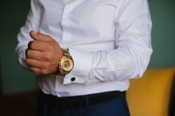 Morning groom. Morning businessman. The man wears a gold watch
