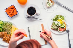 Morning habits of successful people. Day planning and healthy meal. Woman eating carrot and writing in notebook on the served for breakfast white wooden table. Top view, Selective focus