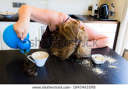 Morning hangover, monday mood, feeling of hard daily work.  Woman with a hard knock life spills cofee and oatmeal in kitchen on table.  Artistic setup of working people life. Stock photo ©