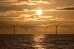 Morning has broken. Offshore wind farm with beautiful sunrise. Religious or spiritual background image. Peaceful tranquil scene of hope, global warming, climate change and environmental conservation.