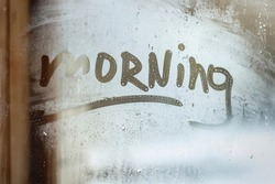 morning inscription on the window glass in cold day. Cozy home concept
