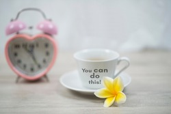 Morning inspirational motivational quote - You can do this. On a cup of morning coffee with alarm table clock and yellow frangipani flower on white table background. Positive affirmation words.