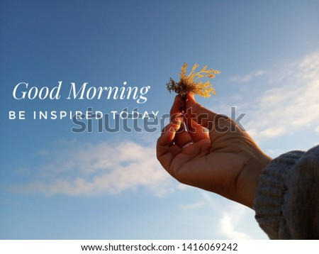 Morning inspirational quote- Good morning. Be inspired today. With blurry image of  young woman hands holding sea weed against the bright and blue sky on a sunny day welcoming summer season.