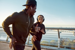 Morning is the best time for jogging. Young happy african couple or friends in headphones running together on the bridge, they talking and smiling during run. Sport. Active morning. Healthy lifestyle