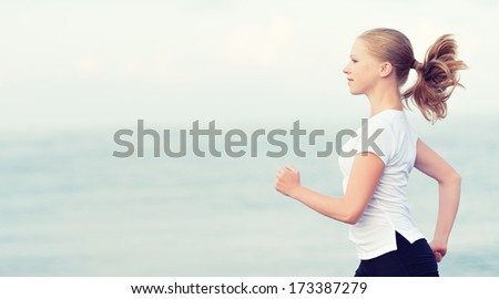morning jog. young woman running on the beach on the coast of the Sea