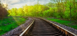 Morning landscape on the railway tracks. The sun's rays are the green grass and the rails on which the train travels. Trees along the railway.