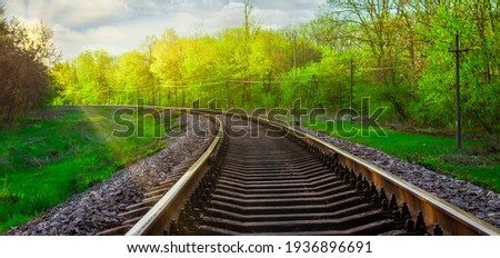 Morning landscape on the railway tracks. The sun's rays are the green grass and the rails on which the train travels. Trees along the railway. Сток-фото ©