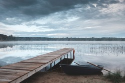 Morning landscape. The shore of the lake with a wooden pier and tied the boat at dawn. The water reflects the sky. A light fog is spreading over the water. As a concept of outdoor recreation.