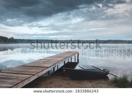 Morning landscape. The shore of the lake with a wooden pier and tied the boat at dawn. The water reflects the sky. A light fog is spreading over the water. As a concept of outdoor recreation. Foto d'archivio ©