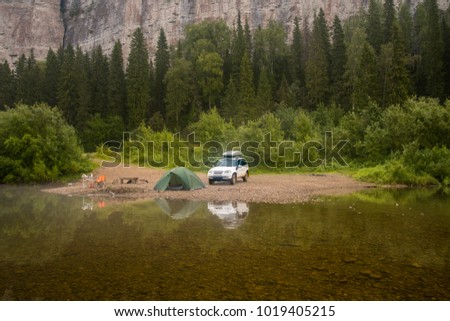 Morning landscape with a tent and 4wd car, the river bank and rocks in the background. Summer camping. Tourism.