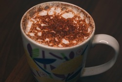 Morning large cup of coffee with milk and spices. Coffee for cheerfulness. Milk foam with ground cinnamon and cardamom. Coffee break