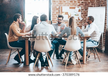 Morning meeting. Group of six young people discussing something while sitting at the table in office together #370389176