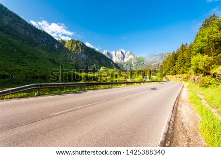 Morning mist over asphalt road in Austrian landscape with forests, fields, pastures and meadows #1425388340
