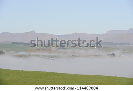 Morning mist rises over a valley in the foothills of the Drakensberg,kwazulu Natal, South Africa