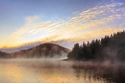 Morning misty fog at the lake, mountains forest landscape and colorful clouds