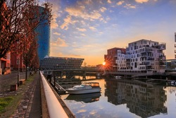 Morning mood in a residential area. Sunrise with sun rays between the buildings. River course in the west port of the city of Frankfurt. Street with trees, bench and boat in the harbor.