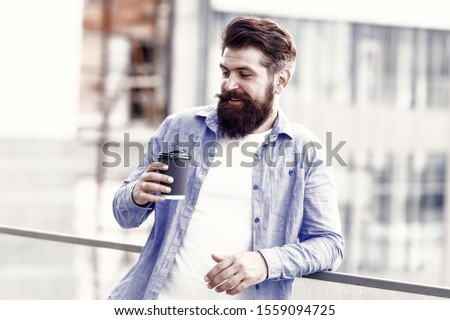 Morning needs caffeine. Bearded man drink hot caffeine drink outdoor. Hipster hold cup with caffeine energy drink. Coffee caffeine boosts my energy level, vintage filter.
