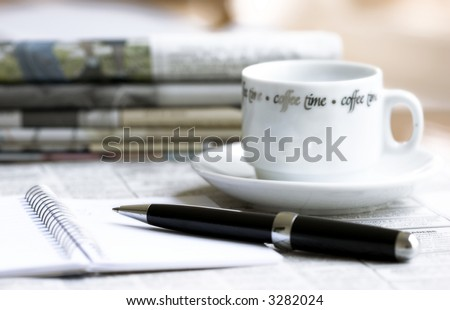 morning newspapers, cup of coffee and pen with notebook