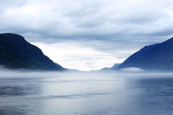 Morning norwegian landscape with mountains and mist over the lake