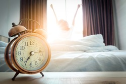 Morning of a new day, alarm clock wake up woman sitting in the room. A woman stretch the muscles at window. Health and care concepts