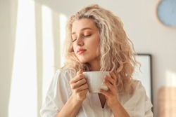 Morning of beautiful young woman drinking coffee in bedroom
