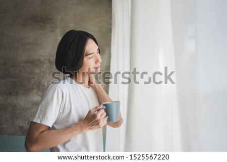 Morning Relaxation. Happy Asian man relaxing and enjoying coffee on holidays. Standing, Eyes closed, Breathing Fresh air.