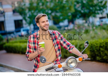 Morning ride. A handsome ma having coffee while riding scoter Zdjęcia stock ©