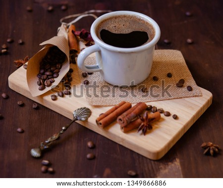 Morning ritual and routine: cup of hot coffee with spices. Lifestyle, good mood for a good day. Coffee beans in a craft paper cornet, anise and cinnamon on a white wooden board. Vintage spoon as decor