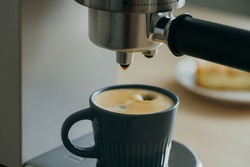 Morning ritual at breakfast with pouring coffee from coffee machine, drops of espresso dripping from coffee maker to small mug. Authentic everyday routine tasks, making hot drink. Soft Focus