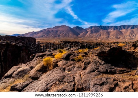 Morning rocky landscape with dark ravine on left gives way to barren desert mountains under bright blue sky with white clouds.