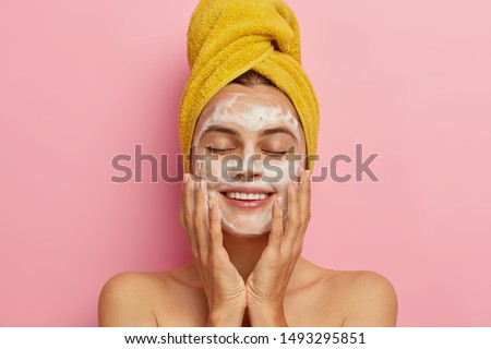 Morning routine and relaxing time concept. Pleased young woman washes face, cleans skin with soap, wears yellow towel on head, keeps eyes shut from pleasure, poses with naked body. Cleansing concept