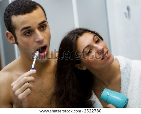 morning routine: the guy brushing his teeth and the girl hairdrying