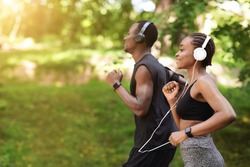 Morning Run Concept. Sporty Black Man And Woman Jogging Outdoor In City Park, Side View Shot With Copy Space