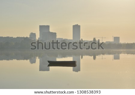 Morning scene in park with single boat floating on the lake surface and skyline of modern buildings reflected in the water. Hazy morning atmosphere. Bucharest, Romania.