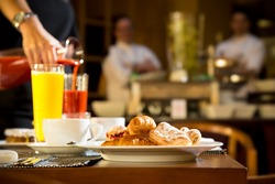 Morning scene of pouring fresh juices at hotel breakfast table