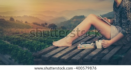 Morning scene of young woman holding coffee cup by right hand and holding small tablet pc while sitting on wood litter on weekend with mountain view in blurry background, processed with vintage effect