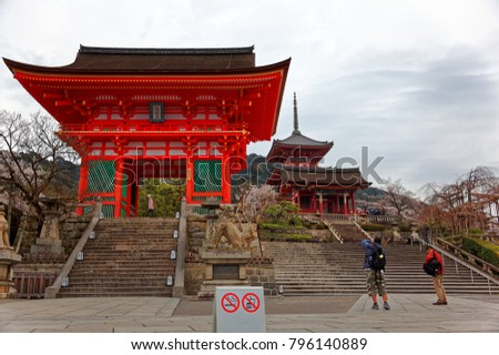 Morning scenery at the entrance to Kiyomizu Dera, a famous Buddhist Temple in Kyoto, Japan, with tourists taking photos of the majestic wooden gate & a traditional Japanese architecture in background