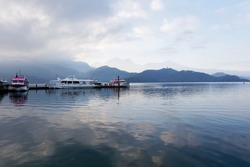 Morning scenery of boats and yachts moored to the docks of Chaowu Pier with mountains under cloudy sky reflected in the peaceful water of Sun-Moon Lake, a famous tourist destination in Nantou, Taiwan