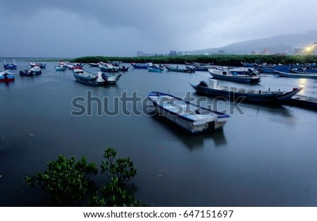 Morning scenery of Tamsui River with motor boats parking on the tranquil water and mangroves in the foreground under moody cloudy sky in Taipei Taiwan #647151697