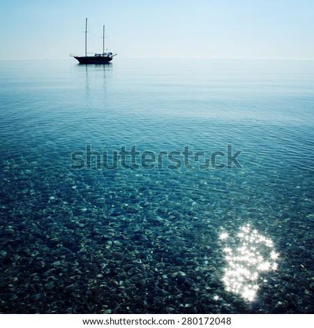Morning sea with boat on the horizon. Aged photo. Sailing ship profile. Toned image. Sunbeams on the sea surface. Calm Sea with a Sailing Vessel. Cirali, Antalya Province, Turkey.