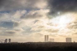 morning smoke fog over city park and high-rise houses on horizon