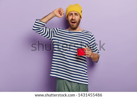 Morning starts with coffee. Sleepy man stretches after waking up, drinks hot beverage to feel refreshed, holds red cup, says good morning, wears casual clothes. People, awakening, drinking concept #1431455486