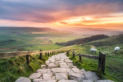 Morning sun casting golden light on the landscape at Mam Tor in the English Peak District.
