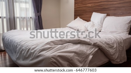 Morning Sunlight Falling On The Bed With A Crumpled Bedding Sheets And  Pillow Through The Window