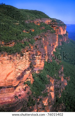 Morning sunlight illuminates a sheer cliff at Blue Mountains National Park of New South Wales, Australia